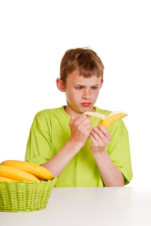 reluctant: Young boy peeling a banana with an expression of distaste and a scowl as he sits at a table with a basket of fresh fruit Stock Photo