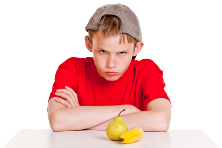 fedup: Single belligerent young boy in red shirt and backward hat with folded arms next to green pear and yellow banana over white background