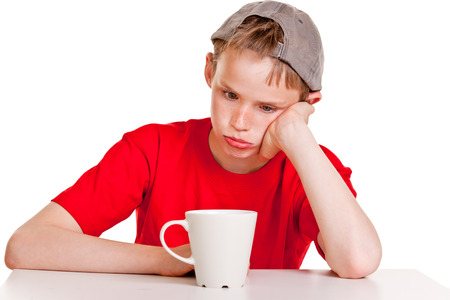 morose: Single young boy in red shirt, backward hat and hand on cheek with bored expression sitting in front of large ceramic mug over white background Stock Photo