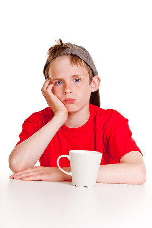 downhearted: Depressed boy in red shirt, gray hat and hand on cheek with bored expression sitting in front of large ceramic mug over white background