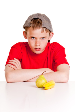 fedup: Defiant young boy sitting at a table with a fresh banana and pear in front of him glowering at the camera with crossed arms as he refuses to eat them