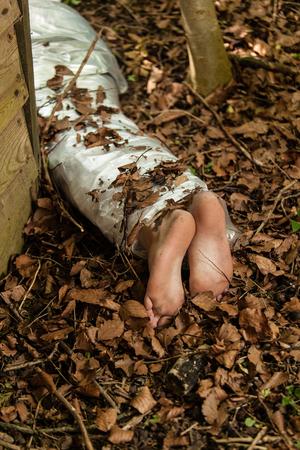 concealed: Wrapped barefoot corpse lying in the woods concealed behind a wooden shed in dried autumn leaves, conceptual image