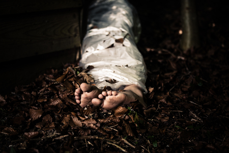 homicide: View of the bare feet of the wrapped body of a homicide victim lying in leafy detritus in the darkness in a conceptual image of violence and crime