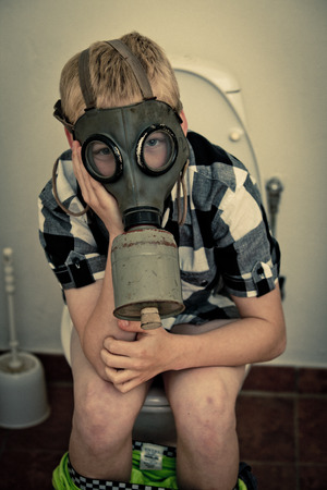 stench: Single blond boy in gas mask sitting on toilet in bathroom with pants down and hands on face