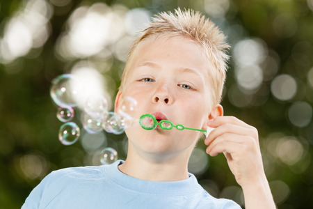 spiky hair: Close up of cute little blond boy with spiky hair and blue shirt blowing bubbles from green wand outdoors Stock Photo