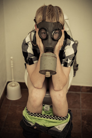 Single male child in gas mask sitting on toilet in bathroom with pants down and hands on face
