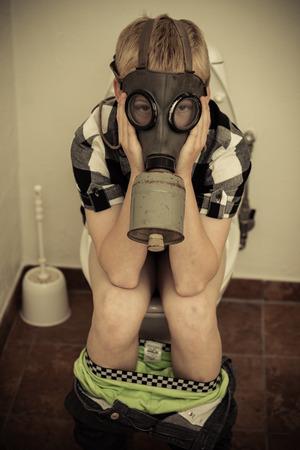 pantalones abajo: Un solo ni�o var�n en la m�scara de gas que se sienta en el inodoro en el ba�o con los pantalones abajo y las manos en la cara Foto de archivo