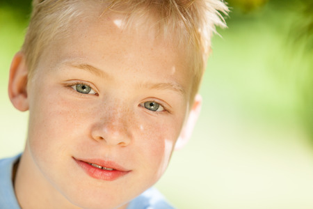 eyes hazel: Close up view on handsome little blond boy with hazel colored eyes in front of obscured green outdoor background