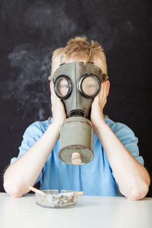 miserable: Miserable child with hands on face covered by chemical gas mask near glass tray of cigarettes on table