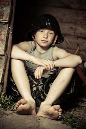 boy barefoot: Calm little boy in large army helmet with number 14 on it sitting on ground while playing army in small clubhouse