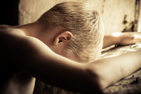 dirty blond: Single blond poor shirtless little boy with head down near window in dirty room with mildew and mold on walls Stock Photo