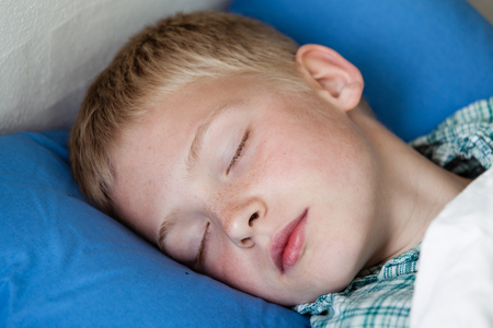 niños rubios: Cerca de lindo niño rubio bajo manta blanca en cama azul dormido con los ojos cerrados en pijama de franela