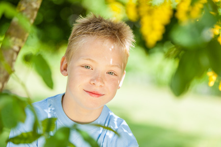 tilted view: Tilted angle view on cute smiling little blond boy with hazel colored eyes framed by green leaves on tree in shade