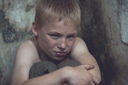 tearful: Weeping abused or imprisoned blond boy curled up with arms around knees in corner of stone walled jail cell Stock Photo