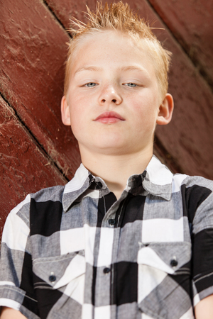 spiked hair: Single handsome little boy in spiked hair and flannel white, black and gray shirt leaning against wall with wood paneling Stock Photo
