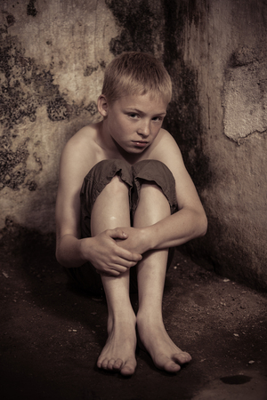 abused: Apprehensive single imprisoned male child wearing shorts sitting on floor with arms around knees in dark, dirty dungeon with stone walls Stock Photo