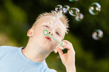 spiked hair: Close up on happy little blond boy with spiked hair and blue shirt blowing bubbles upward from green wand outdoors Stock Photo