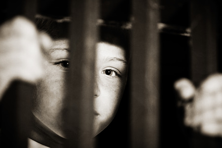 Single abused male child imprisoned with part of face obscured in shadows of jail cell bars and hands