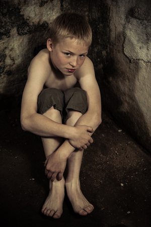 Sad single imprisoned male child wearing shorts sitting on dirty floor in dark, damp dungeon with stone walls Stock Photo