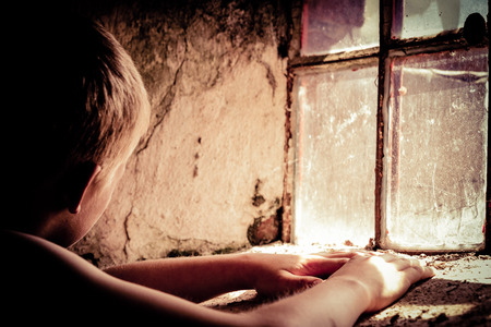 impoverished: Single poor shirtless male child near glass block window in dirty room