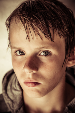 speculative: Thoughtful solemn young boy with wet hair looking at the camera with a speculative expression, close up head shot in shadow