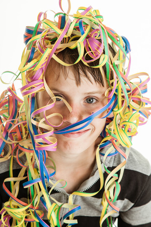 coiled: Smiling young boy celebrating his birthday or a festive holiday or carnival with his head covered in colorful coiled party streamers over white