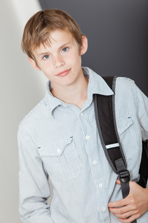 upper body: Handsome young boy with his school backpack slung over his shoulder standing looking at the camera with a quiet smile, upper body Stock Photo