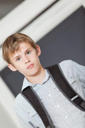 tilted view: Serious young school boy in a tilted angle view standing wearing his backpack indoors at home looking at the camera Stock Photo