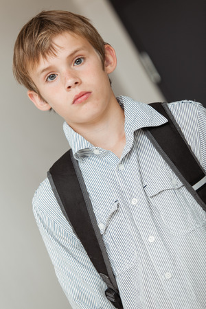 tilted view: Young school boy wearing a backpack, upper body tilted view looking pensively at the camera indoors Stock Photo