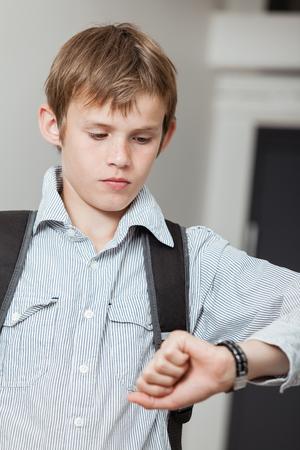 彼は遅刻しないように学校へ彼のエレベーターの彼を待つ、時間の彼の腕時計をチェック バックパックを身に着けている男子生徒