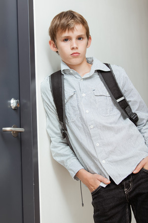 nonchalant: Nonchalant self-assured young schoolboy wearing his backpack leaning against the wall with his hands in his pocket looking at the camera