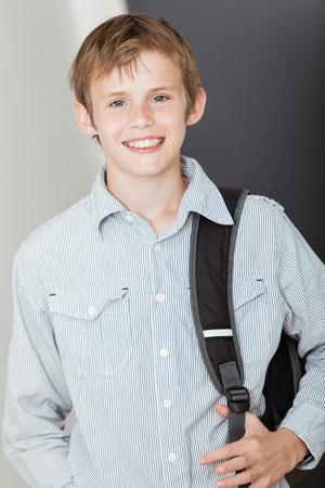 晴れやかな笑顔でカメラを見て彼のバックパックの地位を着て幸せの快活な若い十代の少年の笑顔