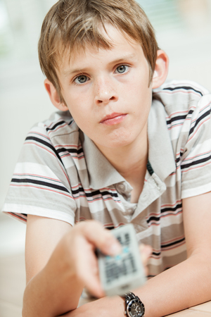 concentrates: Attractive young boy using a remote control pointing it at the camera, focus to his face with a serious intent expression Stock Photo
