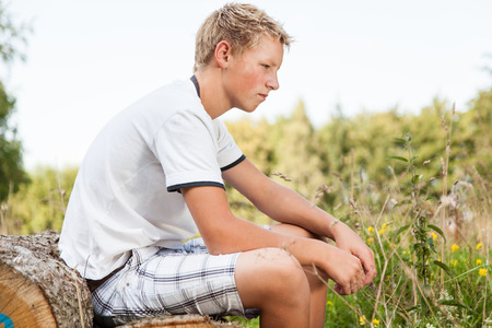introspective: Pensive teenage boy sitting on a wood pile outdoors looking at the ground with a thoughtful expression, side view