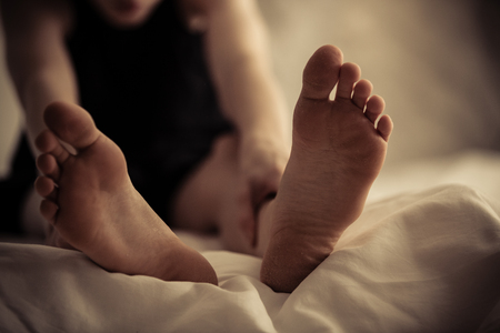 wakening: Single person sitting up with front selective focus view of feet in foreground on bed sheet Stock Photo