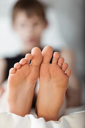 pies masculinos: Vista desde abajo de par de pies que pertenecen a un fuera de foco niño sentado en la cama