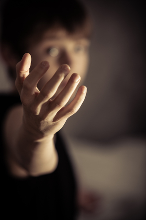 to beckon: Compelling single human hand reaching out from out of focus person as if to call or beckon someone