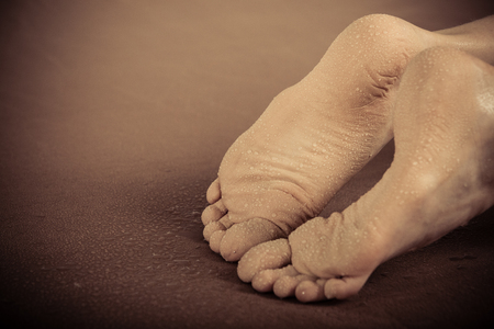 dirty feet: Close up view with copy space on pair of dirty human feet belonging to someone laying face down on carpet Stock Photo