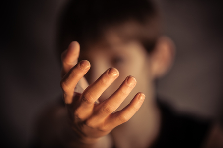 obscured face: Open hand reaching out from obscured face as if to catch, grab or take something Stock Photo