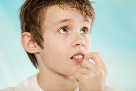 musing: Handsome young boy with worried expression and biting fingernail while looking with copy space over light blue background Stock Photo