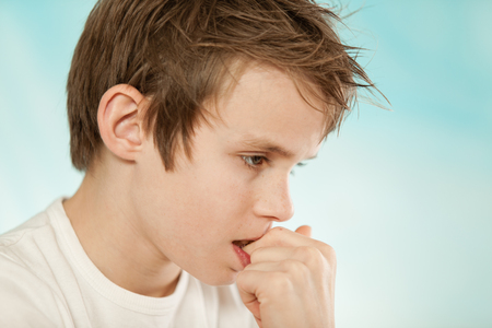 Thoughtful worried young boy biting his nails in trepidation as he stares at the ground with a serious expression, profile head shote on blue with copy space Stock Photo
