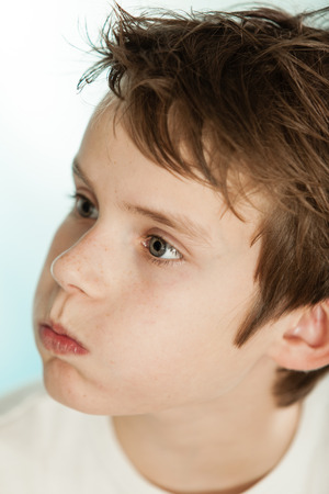 exasperation: Confused young teenage boy blowing out his lips in exasperation, close up head shot portrait Stock Photo