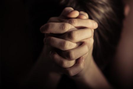 Cierre de vista sobre par de manos juntas en oración según la tradición religiosa cristiana