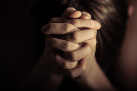 reverent: Close up view on pair of hands folded together in prayer according to Christian religious tradition Stock Photo