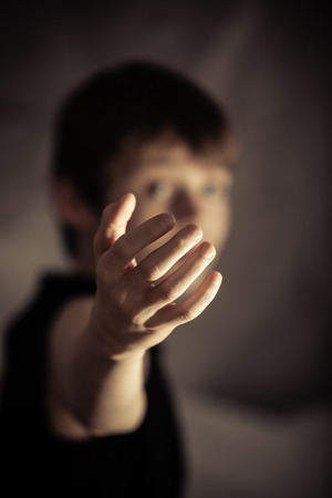 beckoning: Obscured young male with extended arm in beckoning gesture over dark background