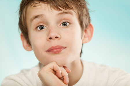 implausible: Sceptical young boy raising his eyebrows in disbelief with a quizzical expression and smile, close up frontal head shot Stock Photo