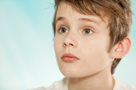 adolescent: Handsome young boy with serious expression listening and looking with copy space over light blue background Stock Photo