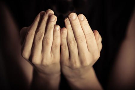 according: Close up view on pair of hands with palms up in prayer according to Islamic tradition