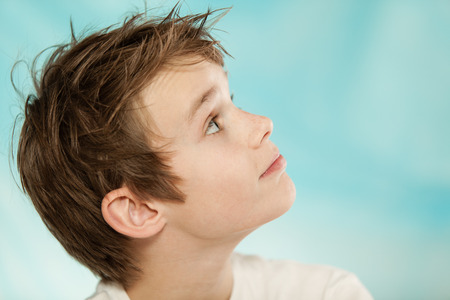 eager: Close up profile view of the head on an eager handsome young boy looking up towards blank blue copy space Stock Photo