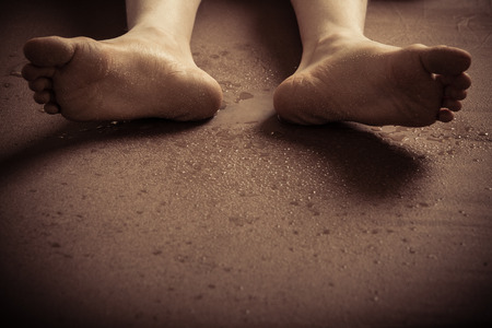 pieds sales: Vue rapprochée sur le fond des pieds sales de personne non identifiable, portant sur son dos sur le sol avec copie espace Banque d'images
